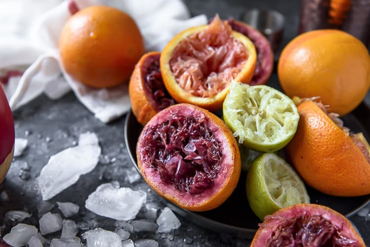 Squeezed oranges and limes from a Sparkling Blood Orange Margarita