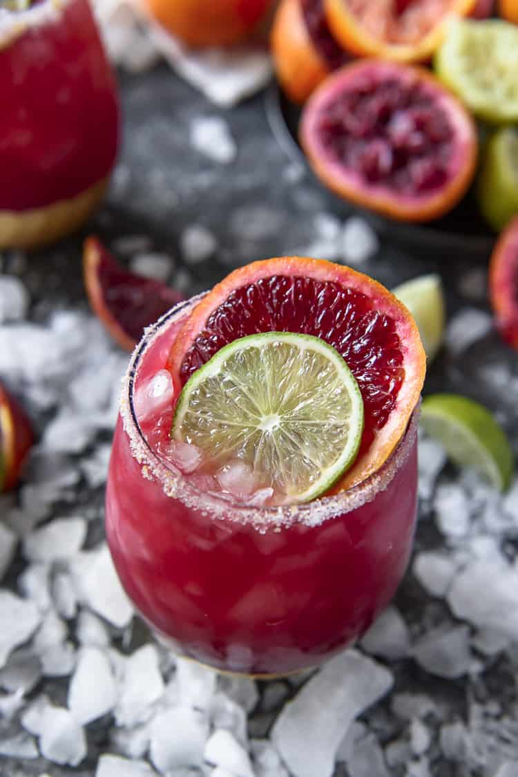 A Sparkling Blood Orange Margarita garnished with lime and orange wheels