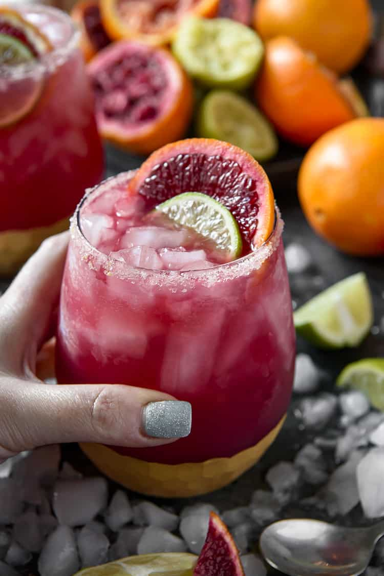 A hand grabbing a Sparkling Blood Orange Margarita