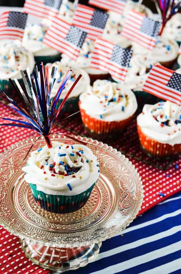 Firecracker Cupcakes | A classic vanilla cupcake, bursting with a slightly tart summer berry compote, and crowned with a halo of fluffy whipped cream cheese frosting.