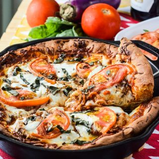 Eggplant Parmesan Caprese Skillet Pizza | A delicious deep dish caprese skillet pizza, layered with crispy baked eggplant parmesan, fresh tomatoes, spinach, & basil, and creamy mozzarella cheese.