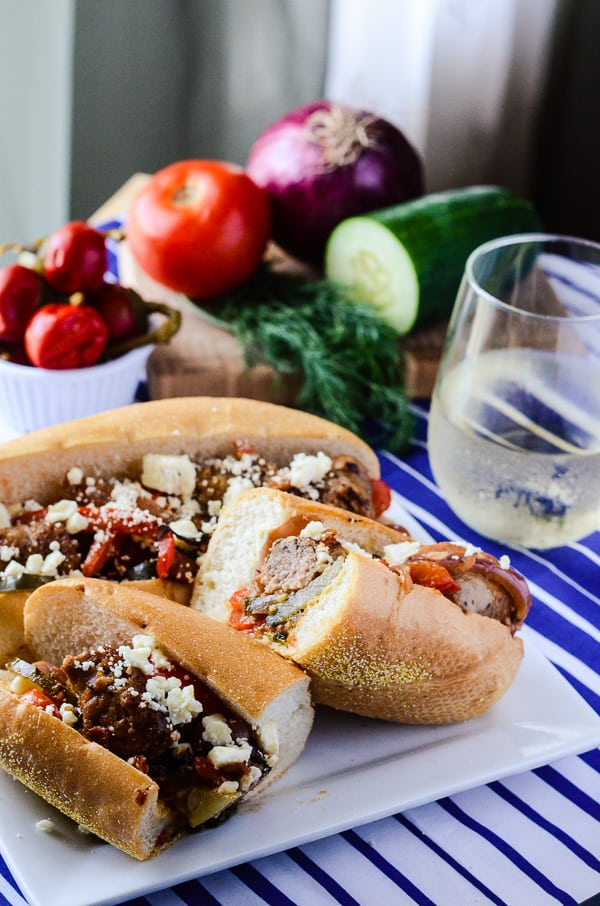 Greek-Style Sausage & Peppers Sandwich | A simply perfect classic sausage and peppers sandwich, made in one pan and taken to foreign places by the use of dill, cucumber, and Nikos® Feta Cheese!