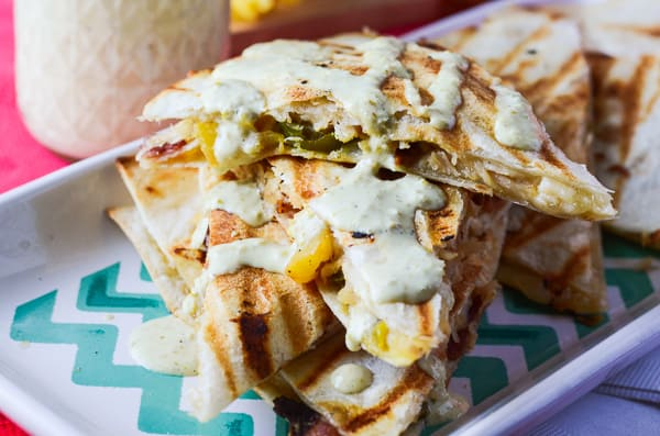 Spicy Pineapple Chicken Quesadillas with Jalapeno Lime Aioli | Caramelized pineapple and crispy bacon give these chicken quesadillas a sweet, smoky flavor, and are given a kick with a spicy jalapeno lime aioli drizzle.
