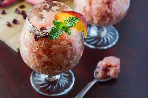 Peach Pomegranate Mojito Granita | Made with fresh mint simple syrup and ripe Georgia peaches marinated in PAMA Pomegranate Liqueur, this fancy shaved Italian ice is a true crowd-pleaser!