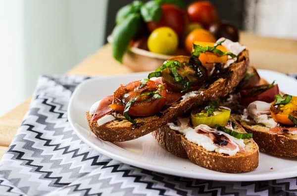 Burrata Caprese Crostini with Prosciutto | A creamy twist on a classic caprese crostini - toasted ciabatta topped with burrata, prosciutto, mini heirloom tomatoes, basil & balsamic.