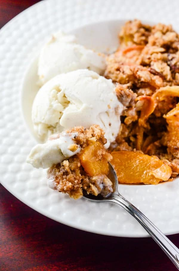 Cinnamon Ginger Peach Crisp | A a spicy, playful nod to fall, using one of summer's favorite fruits marinated in cinnamon whiskey and fresh ginger!