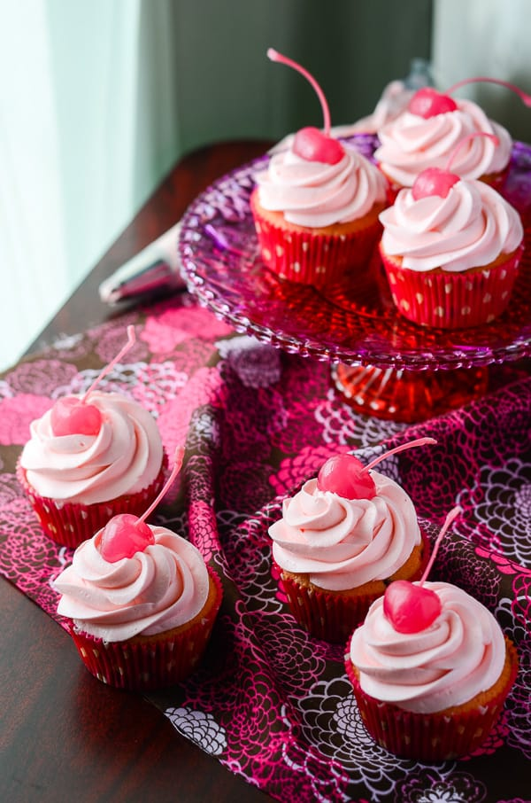 Cherry Chocolate Chip Cupcakes with Pink Chocolate Buttercream | Think pink! These delightful maraschino cherry chocolate chip cupcakes are topped with a fluffy pink chocolate buttercream, and were baked (and eaten!) for a great cause!