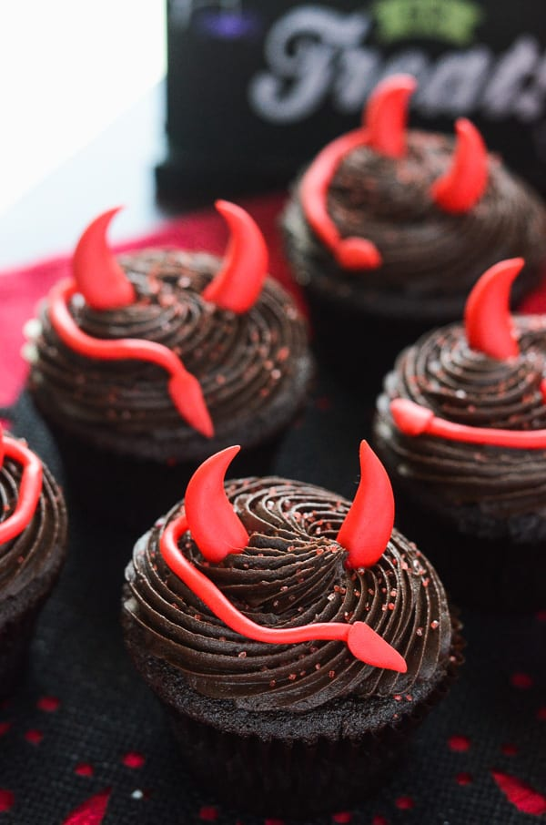 These Spicy Little Devil's (Food) Cupcakes turn up the heat with cinnamon & cayenne, and are topped with devilish decor perfect for any Halloween party!