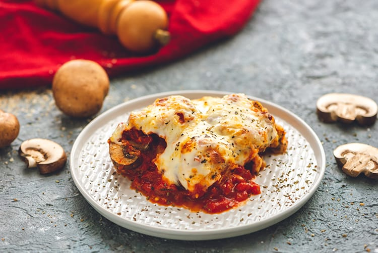 A slice of Baked Eggplant Parmesan on a plate with mushrooms scattered around