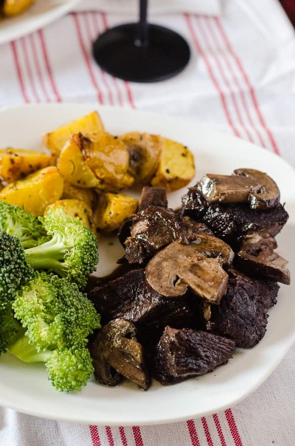 Red Wine Mushroom Braised Beef | Tender, juicy beef, braised in a delicious red wine & mushroom gravy - served with herbed roasted potatoes and your favorite veggie, it makes for a wonderful Sunday Supper!
