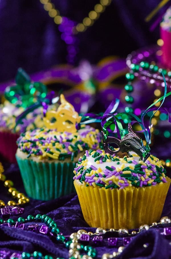 King Cake Cupcakes | Laissez les bons temps rouler! Celebrate Mardi Gras with these fun and festive moist vanilla cupcakes, swirled with cinnamon sugar and topped with cream cheese glaze and festive sprinkles!