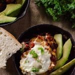 Eggs in Purgatory | Breakfast with a bit of burn! Eggs poached in a spicy, garlicky tomato sauce, served over crusty bread and with a side of cooling avocado slices.