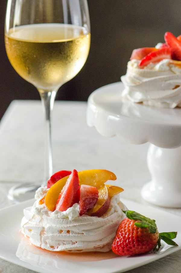 Mini Strawberry Peach Pavlovas | Helloooooooo spring! Welcome the season with baked meringue shells, filled with fresh whipped cream and Chardonnay-marinated strawberries & peaches.