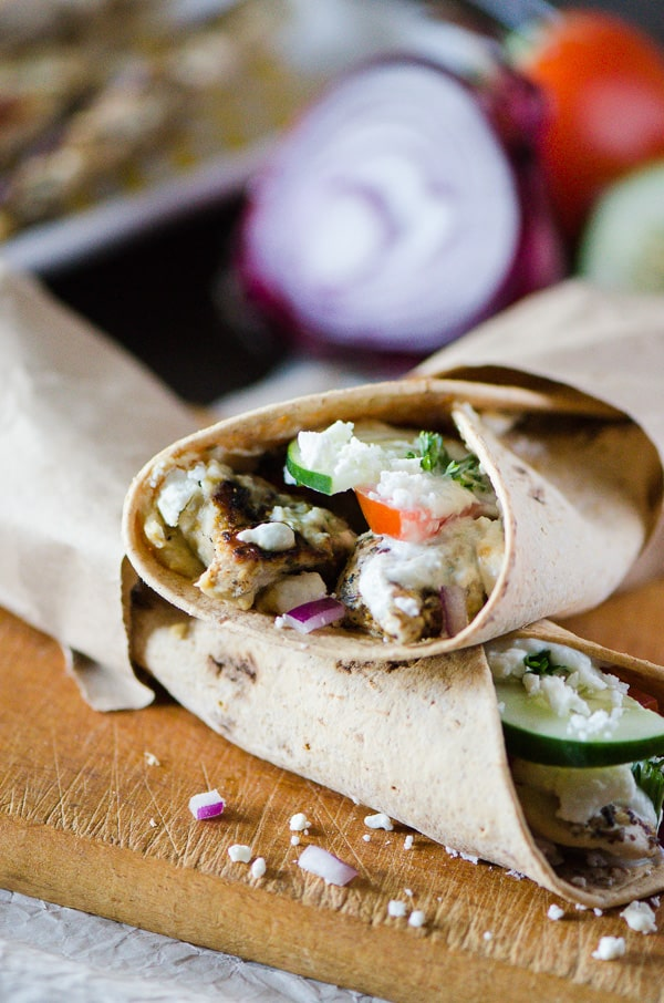 Souvlaki Chicken Wraps with Homemade Tzatziki | Flatbread stuffed with hummus, souvlaki chicken, veggies, feta cheese, and homemade tzatziki, these easy Greek-style wraps are perfect for lunch on the go or a fun Sunday Supper!