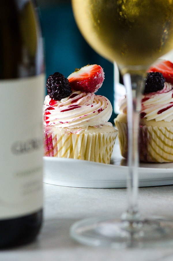Vanilla Red Wine Berry Cupcakes | Fluffy vanilla bean cupcakes overflowing with a Pinot Noir berry filling, and topped with a berry Italian meringue buttercream - a perfect spring dessert!