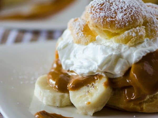 Banoffee Cream Puffs | A twist on an English dessert - bananas, toffee, and whipped cream, taken out of the pie crust and nestled in a light, fluffy homemade cream puff!