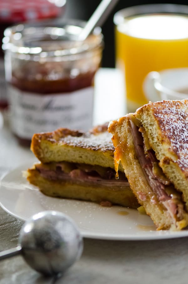 French Toast Monte Cristo | Truly the ultimate breakfast sandwich! Turkey, ham, bacon, lots of cheese, fried egg, and tasty preserves, tucked between two slices of thick, lightly sweetened challah French toast.
