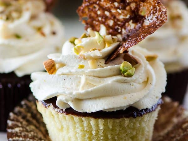 Cannoli Cupcakes with Chocolate Pistachio Crunch | Holy cannoli, what a cupcake! These vanilla-almond Cannoli Cupcakes are stuffed and topped with a classic sweet ricotta filling, glazed with a layer of chocolate ganache, and garnished with some pretty fancy food art.