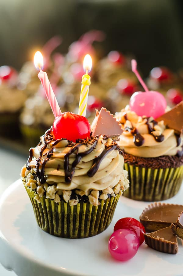 Take a bite of cupcake heaven! Tender chocolate cupcakes, stuffed with hot fudge sauce and topped with peanut butter mousse, these decadent Peanut Butter Hot Fudge Sundae Cupcakes won't melt like ice cream...but you might need a glass of milk to wash them down!