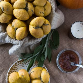 Perfect dinner rolls with a fall twist! These Pumpkin Sage Cloverleaf Rolls are slightly sweet, super fluffy, and smothered in melty sage compound butter.