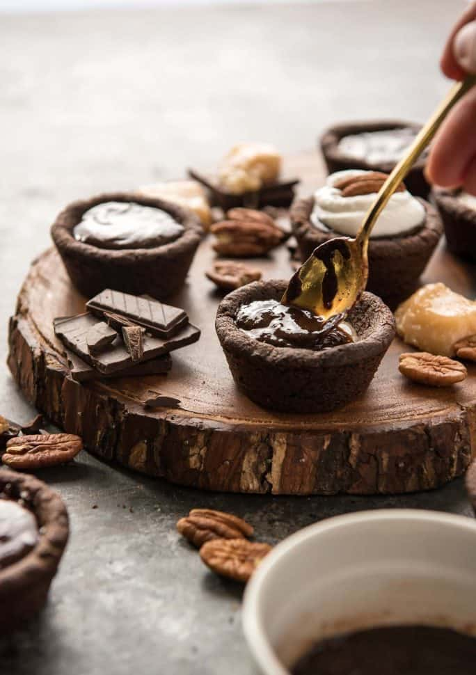 Chocolate Turtle Pie Cookie Cups filling with ganache