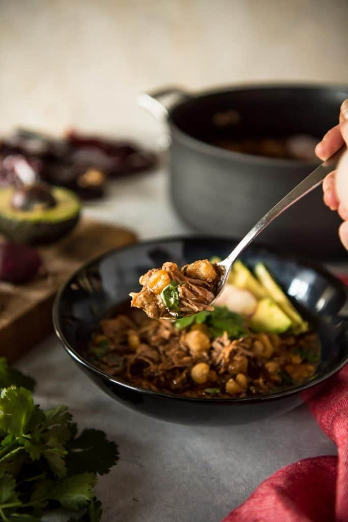 Posole Rojo: The Best Pork and Hominy Stew spoon of stew