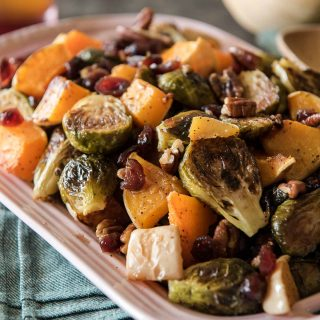 Caramelized veggies, roasted with pecans and tossed with a sweet and tangy glaze - these Roasted Brussels Sprouts & Squash With Cranberry Cider Glaze might be the perfect holiday side dish!