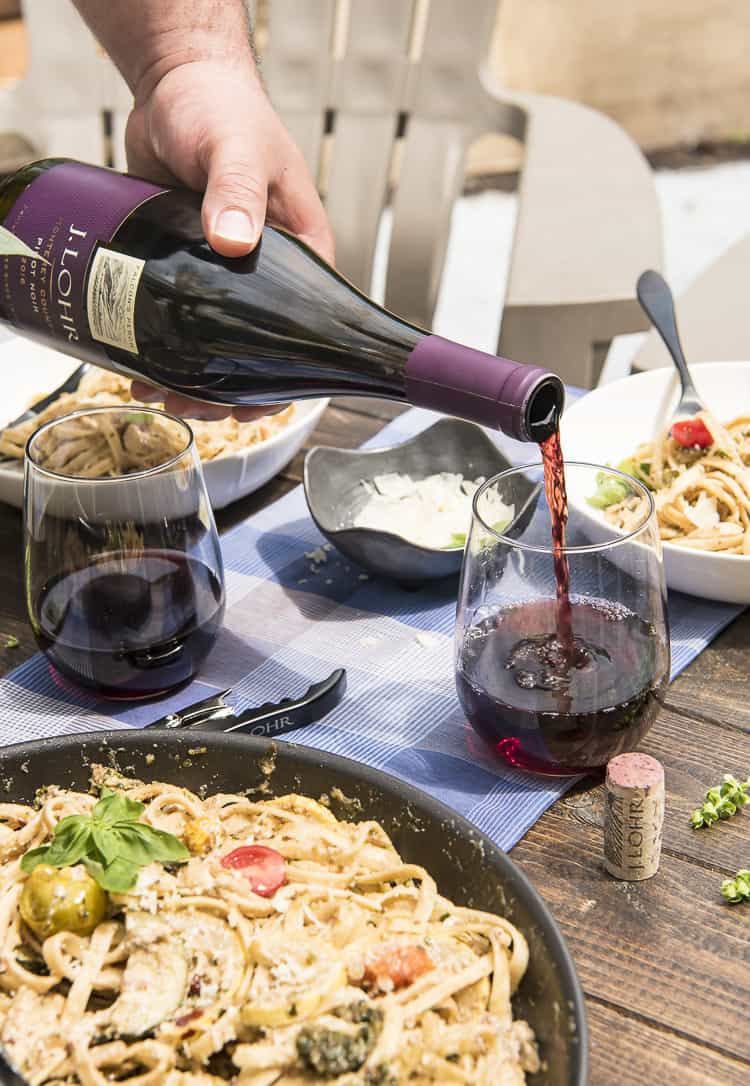 Summer Vegetable Ricotta Pesto Pasta with wine pouring