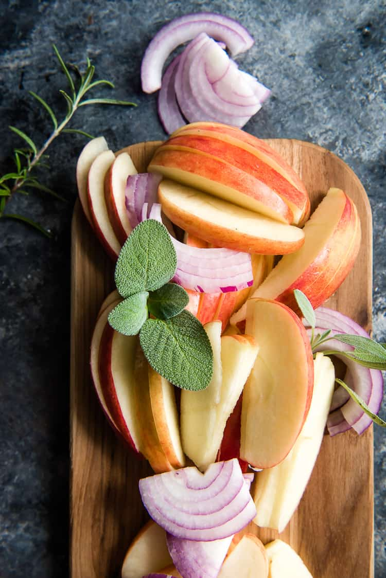 red onions, apples, and herbs on a cutting board