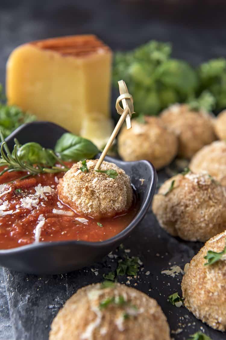 Italian Arancini balls dipped in marinara sauce