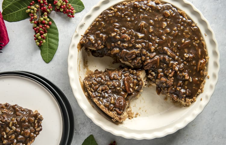 Pecan Pie Cheesecake in pie pan with slice missing