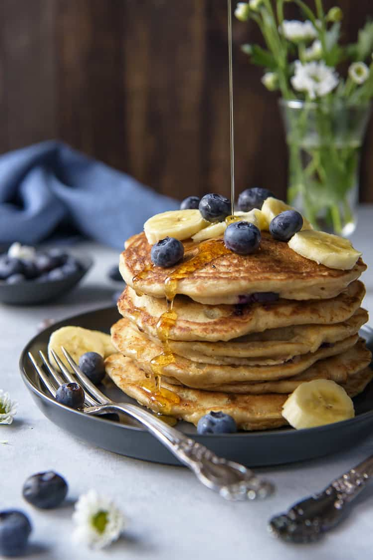 Drizzling maple syrup on a stack of Blueberry Banana Pancakes