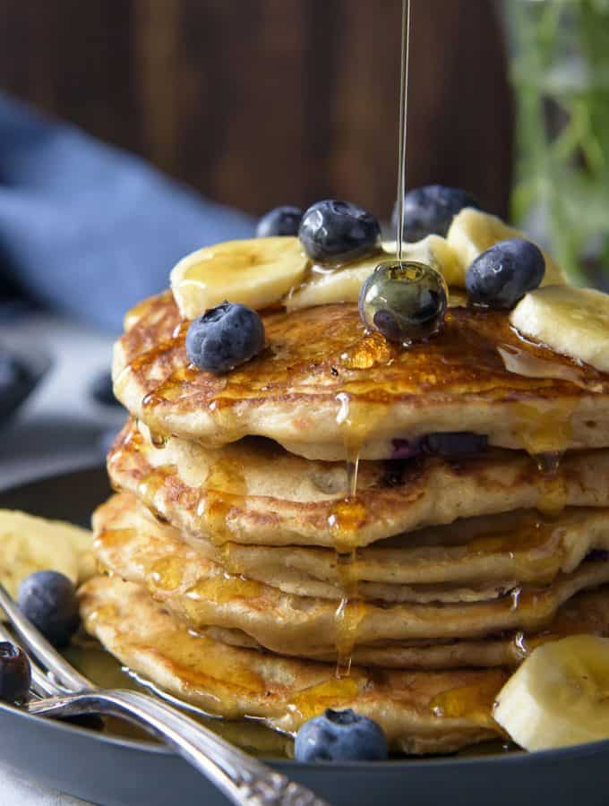 A closeup of syrup being drizzled on a stack of Blueberry Banana Pancakes