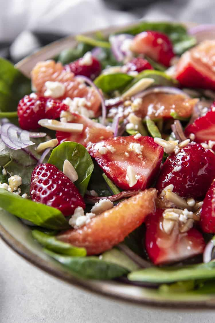 A Citrus Strawberry Spinach Salad with feta cheese, almonds, and balsamic vinaigrette dressing