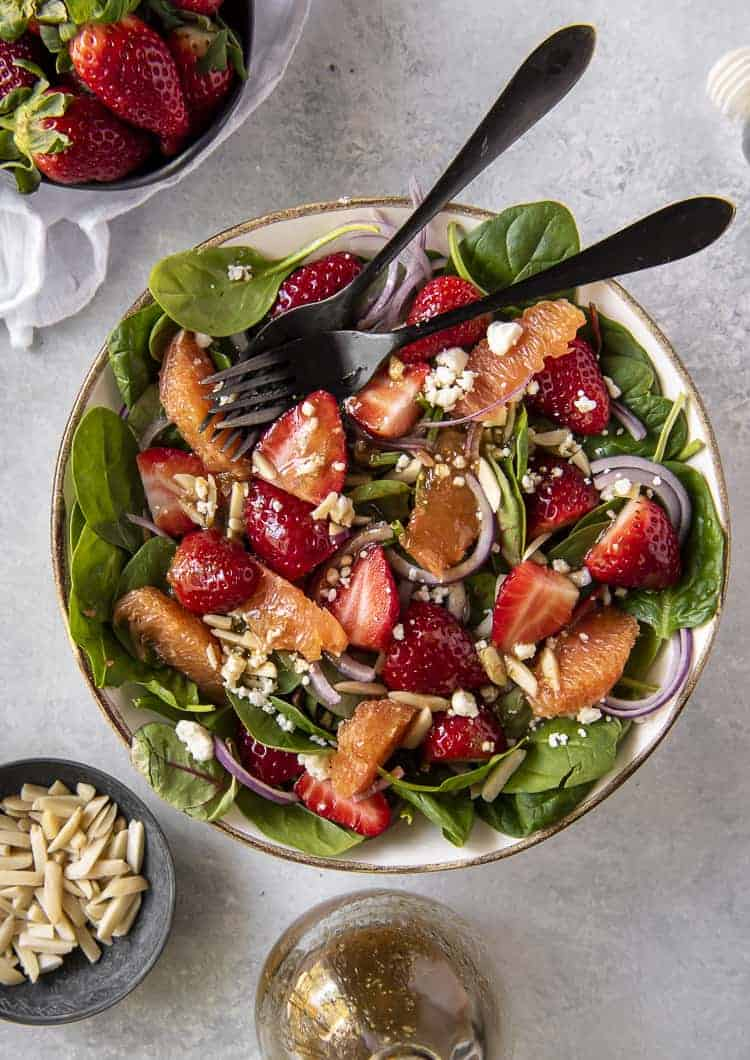 Two forks balanced in a bowl of Citrus Strawberry Spinach Salad