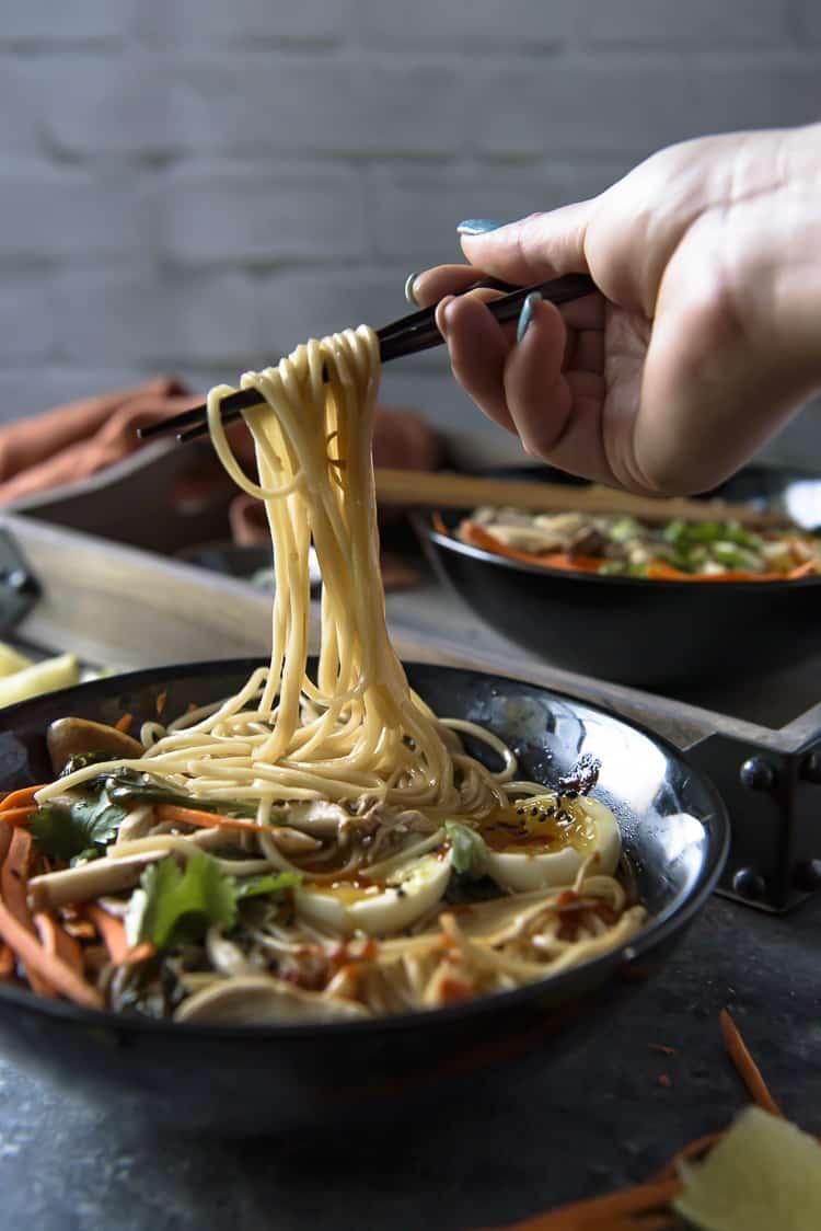 Lifting ramen noodles from a bowl of chicken ramen