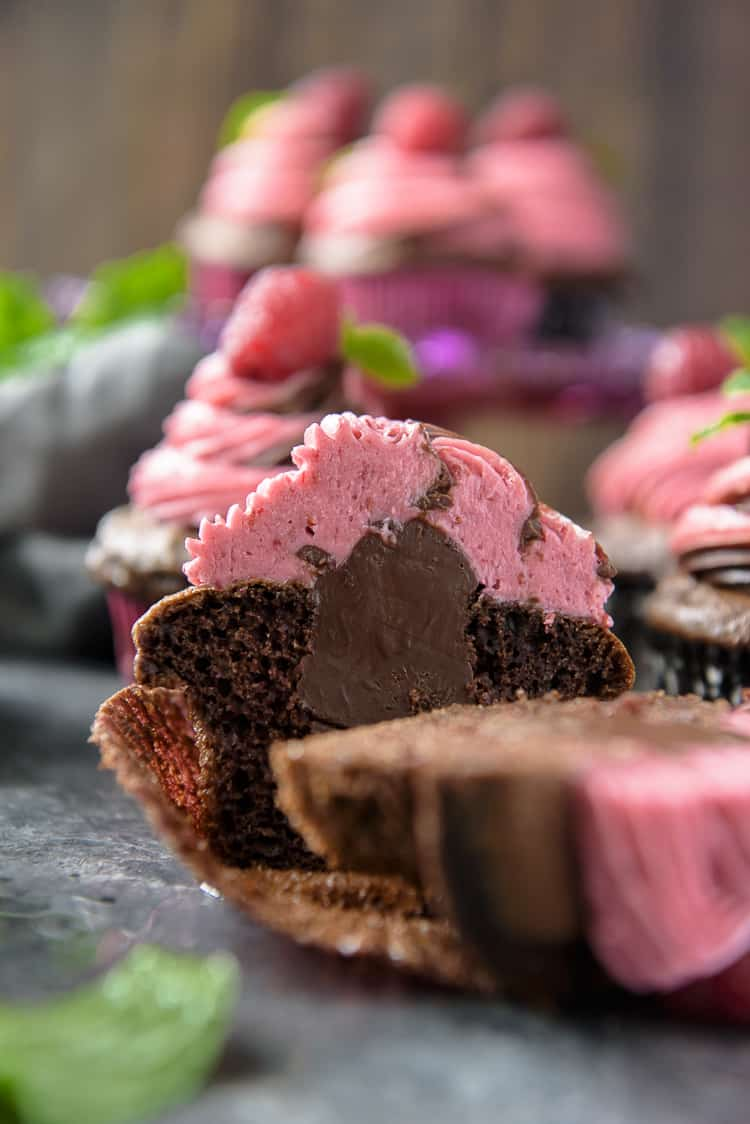 A cut Chocolate Cupcake with raspberry buttercream