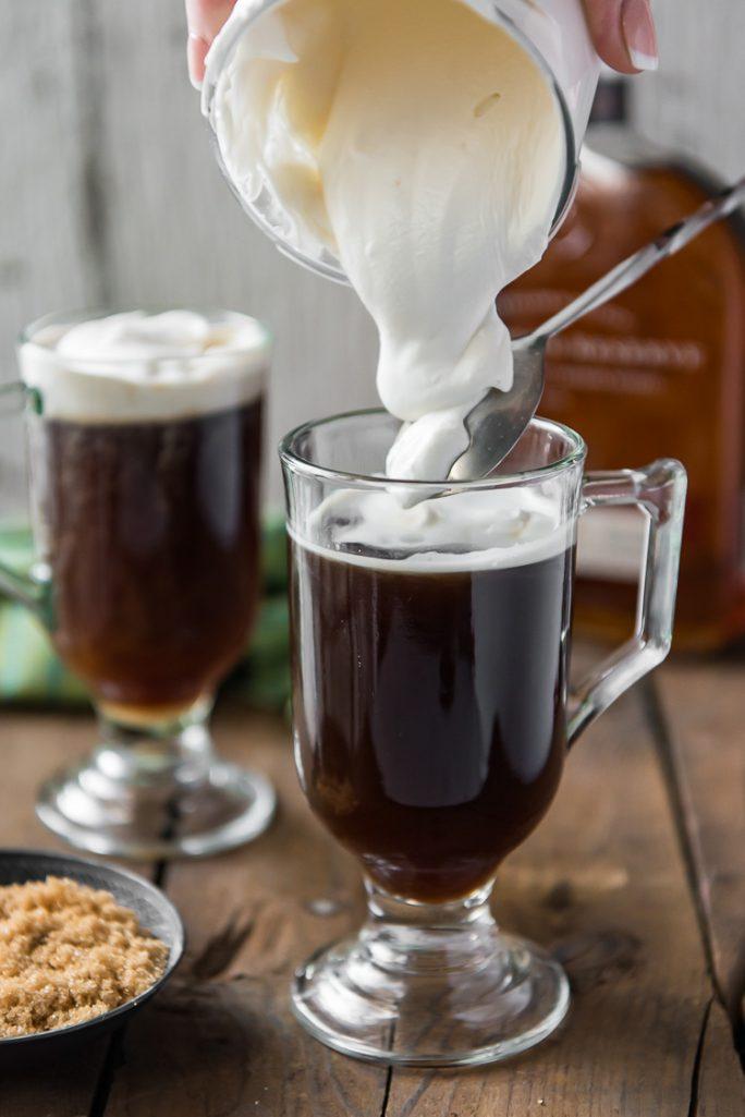 Spooing cream over an Irish Coffee