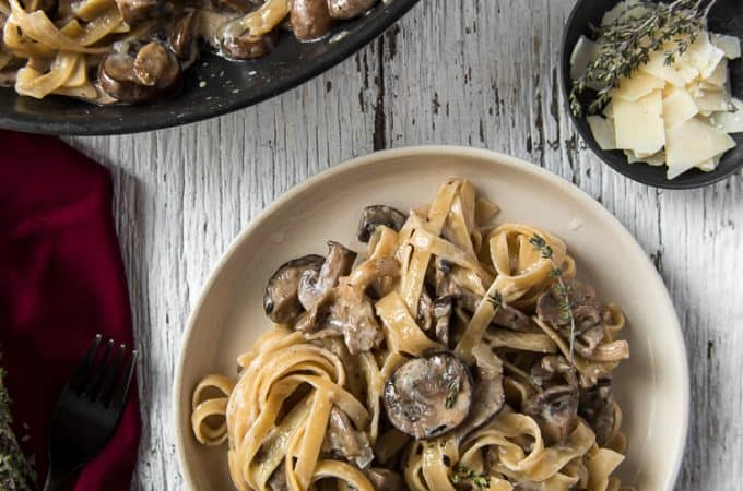 A plate and skillet full of Creamy Brown Butter Mushroom Pasta