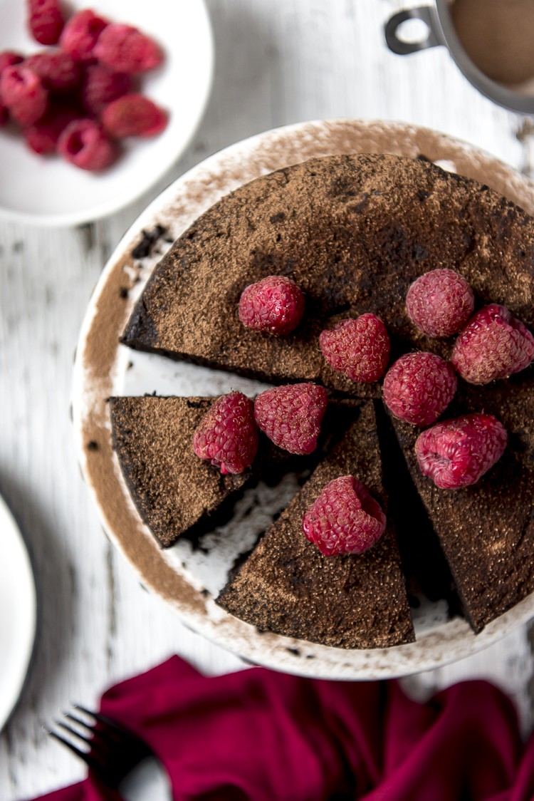 Top shot of a Flourless Chocolate Espresso Cake garnished with fresh raspberries
