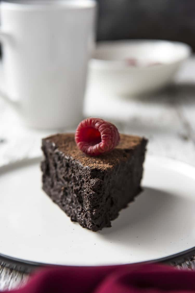 A slice of Flourless Chocolate Cake with a raspberry