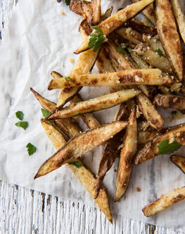 Baked garlic and Parmesan truffle fries on parchment paper