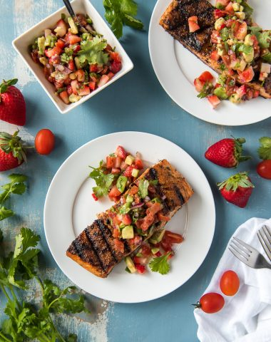 Grilled Salmon on plates with a bowl of Strawberry Salsa