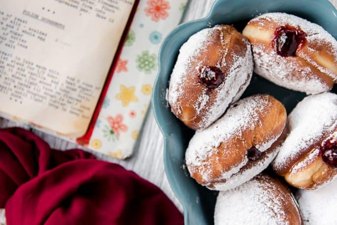 Paczki filled with jam in a dish with a cookbook