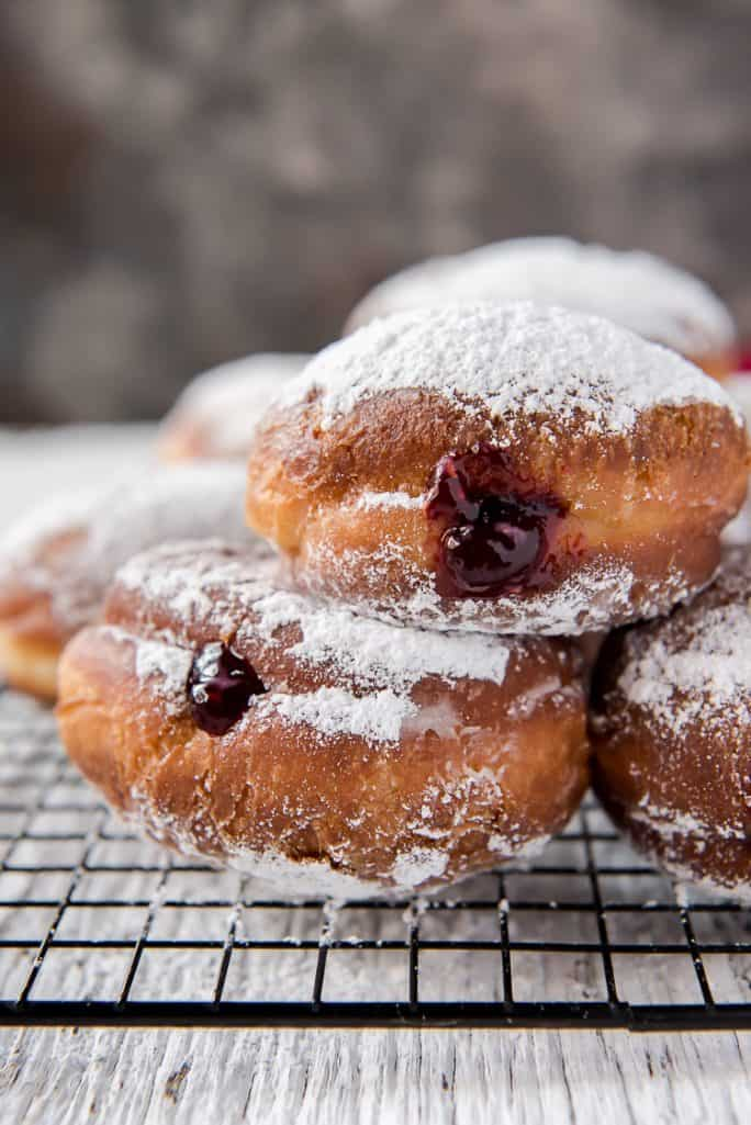 Paczki dusted with powdered sugar on a cooling rack