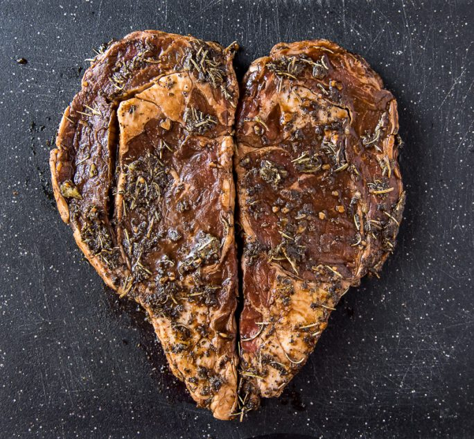 2 marinated ribeye steaks in the shape of a heart