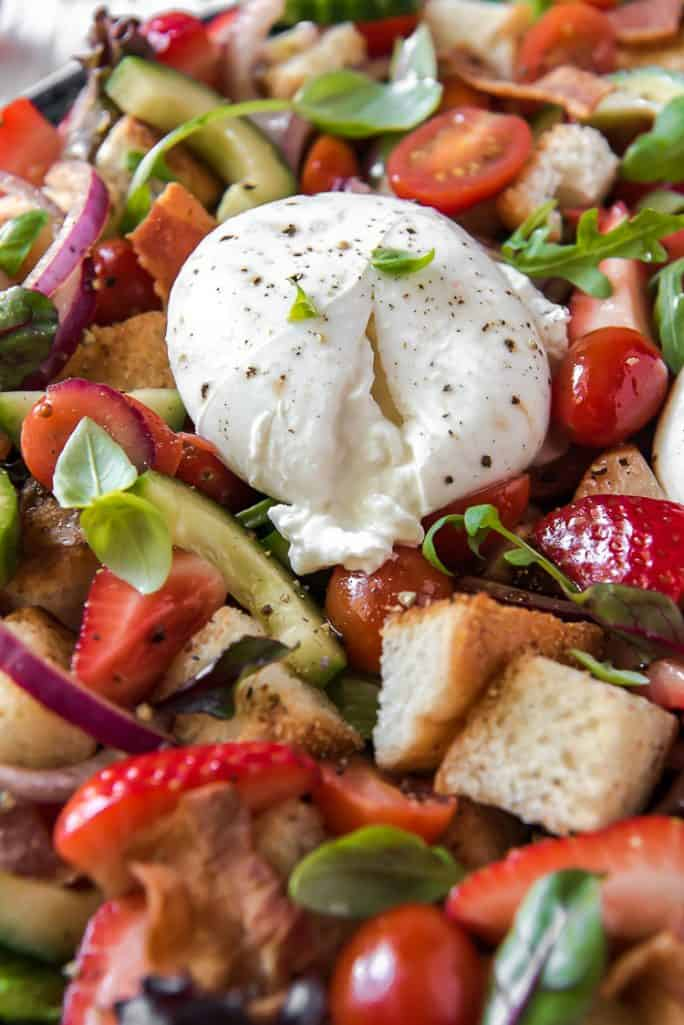 Closeup of burrata cheese in a panzanella salad