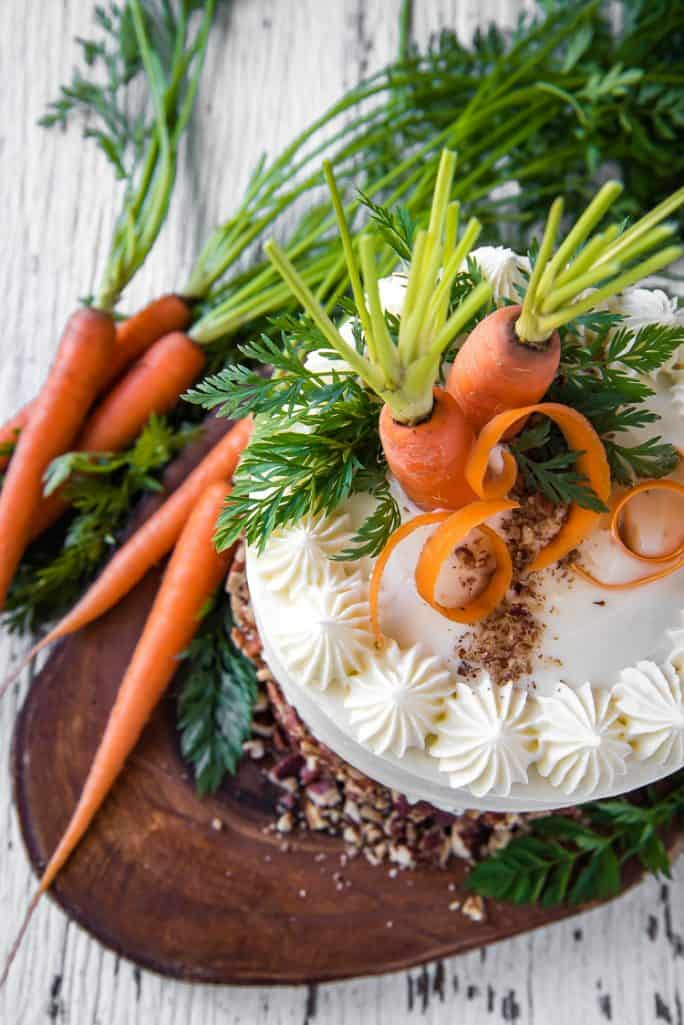 A decorated Buttermilk Carrot Cake on a wooden stand