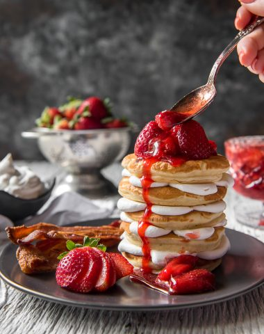 Spooning strawberry sauce on a stack of Strawberry Cheesecake Pancakes