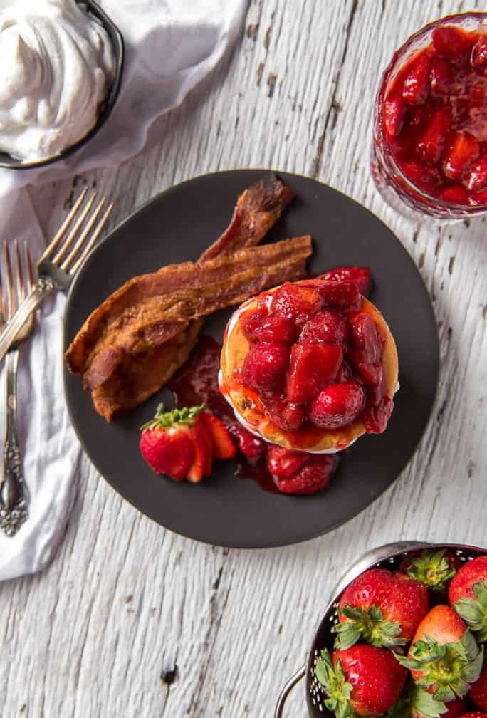 Strawberry Cheesecake Pancakes on a plate with bacon